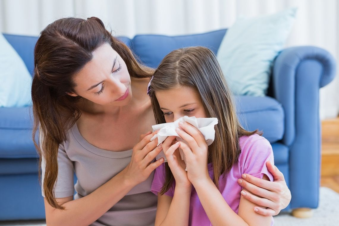 Mother helping daughter with allergies blow her nose at home in the living room